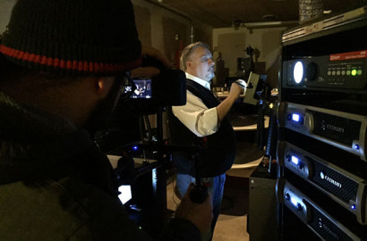 WOSU cinematographer Andrew Ina shooting in a scene Drexel Theatre's projection booth with manager Kevin Rouch