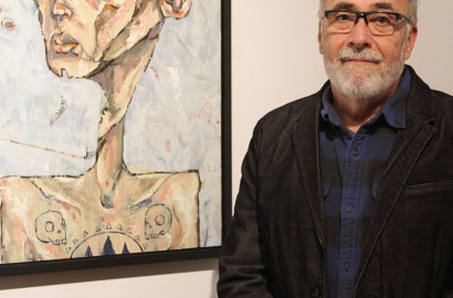 Duff Lindsay poses in front of a Joey Monsoon painting at Lindsay Gallery.