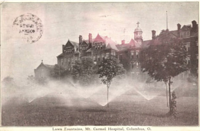 Postcard of the original Mount Carmel Hospital showing sprinklers watering the grass.